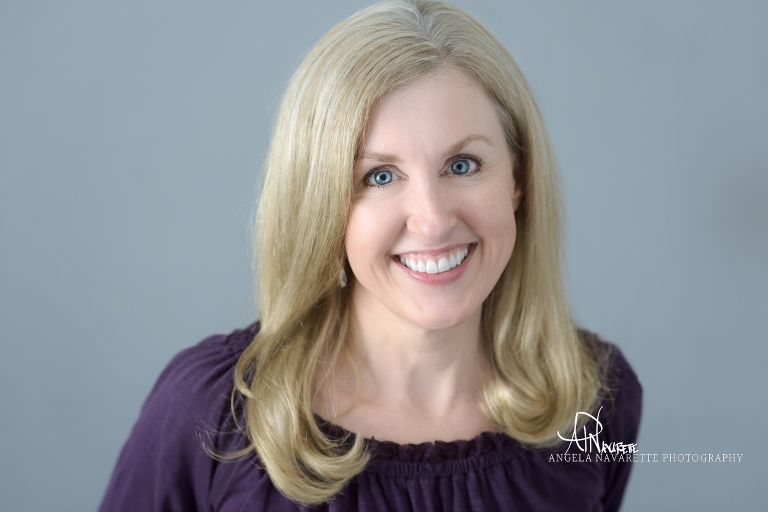 Beautiful Liz Ziske, co-founder of Z Natural life. Business portrait photography of gorgeous blonde with gray background and purple blouse.