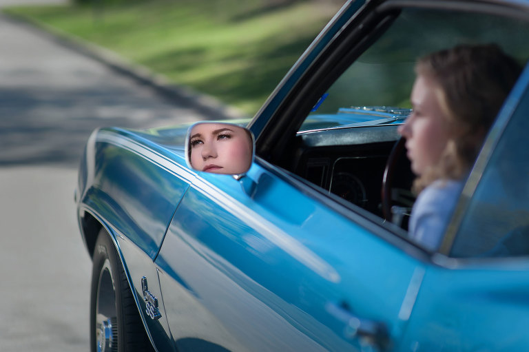 Portrait of a blonde high school senior girl in a blue super sport camaro